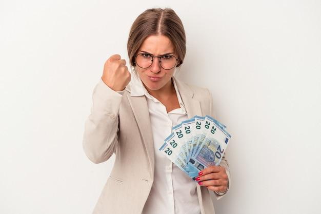 カメラに拳、攻撃的な表情を示す白い背景で隔離の紙幣を保持している若いロシアのビジネス女性。