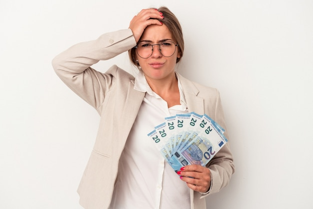 Young russian business woman holding banknotes isolated on white background being shocked, she has remembered important meeting.