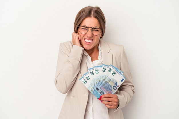 Young russian business woman holding banknotes isolated on white background covering ears with hands.