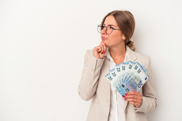 Young russian business woman holding banknotes isolated on white background looking sideways with doubtful and skeptical expression.