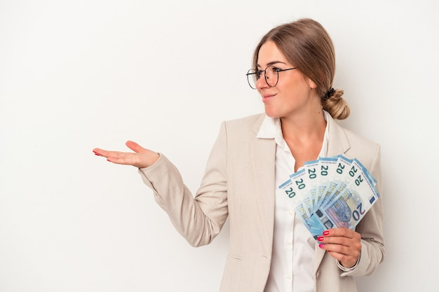 Young russian business woman holding banknotes isolated on white background showing a copy space on a palm and holding another hand on waist.