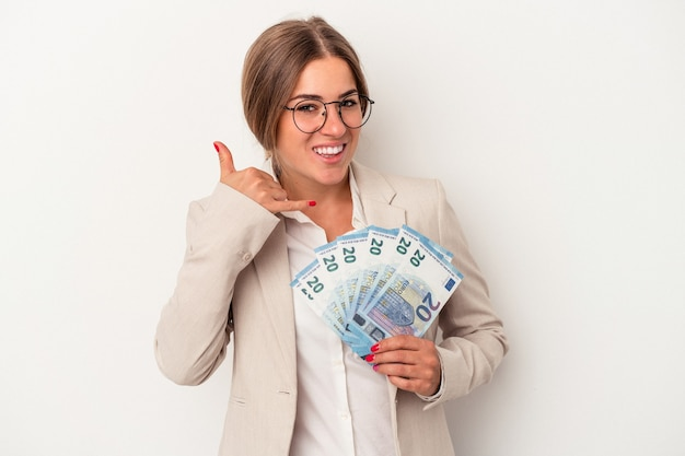 Young russian business woman holding banknotes isolated on white background showing a mobile phone call gesture with fingers.