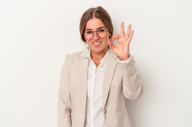 陽気で自信を持って大丈夫なジェスチャーを示す白い背景で隔離の若いロシアのビジネス女性。
