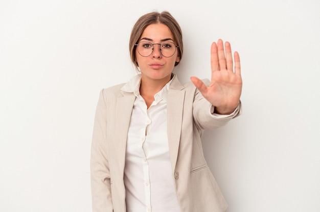 一時停止の標識を示す伸ばした手で立っている白い背景で隔離の若いロシアのビジネス女性は、あなたを防ぎます。