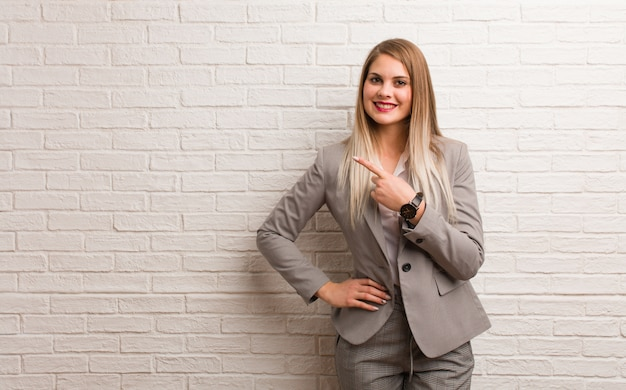 Young russian business woman smiling and pointing to the side