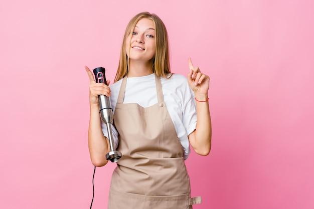 Молодая русская женщина повара, держащая изолированный электрический миксер, показывает обоими указательными пальцами вверх, показывая пустое пространство.