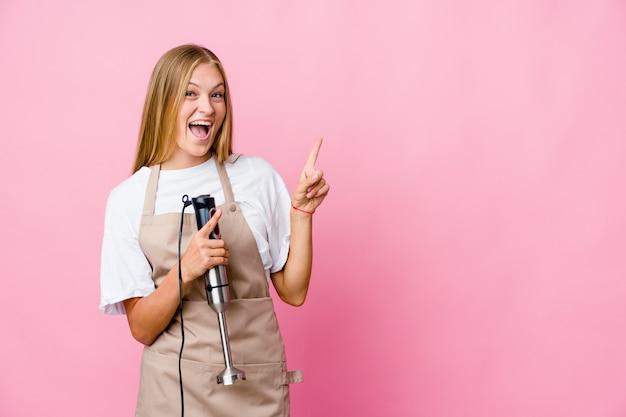 興奮と欲望を表現し、コピースペースに人差し指で指している孤立した電気ミキサーを保持している若いロシア料理人の女性。