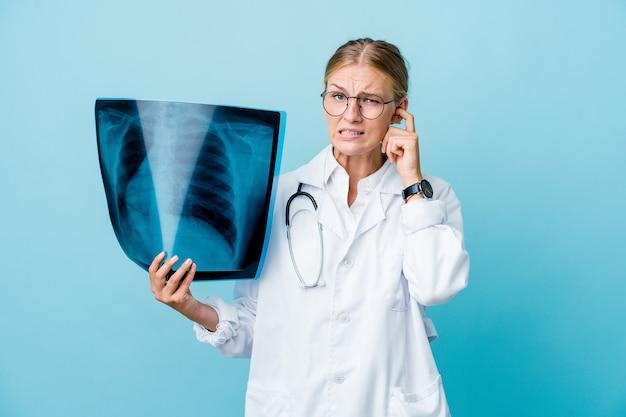 손으로 귀를 덮고 파란색에 뼈 스캔을 들고 젊은 러시아 의사 여자