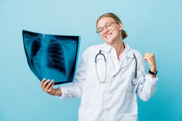 青いダンスと楽しんで骨スキャンを保持している若いロシアの医師の女性。