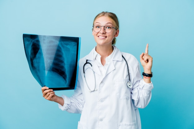 Young russian doctor woman holding a bone scan on blue indicates with both fore fingers up showing a blank space.