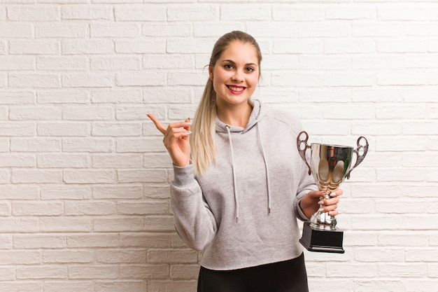 Young russian fitness woman holding a trophy