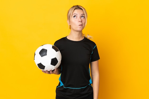 Молодой российский футболист женщина изолирована на желтом и смотрит вверх