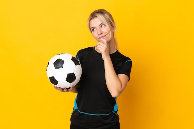 Молодой российский футболист женщина изолирована на желтом фоне и смотрит вверх