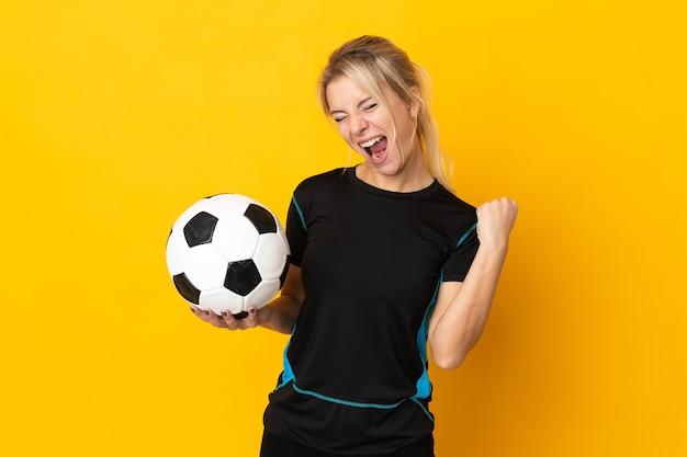 승리를 축하하는 노란색 배경에 고립 된 젊은 러시아 축구 선수 여자