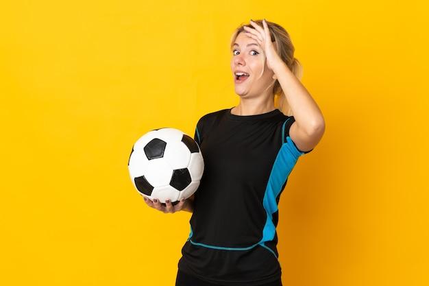 노란색 배경에 격리된 젊은 러시아 축구 선수 여성이 옆을 바라보면서 깜짝 제스처를 하고 있다