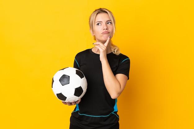 Молодой российский футболист женщина, изолированные на желтом фоне, сомневаясь, глядя вверх