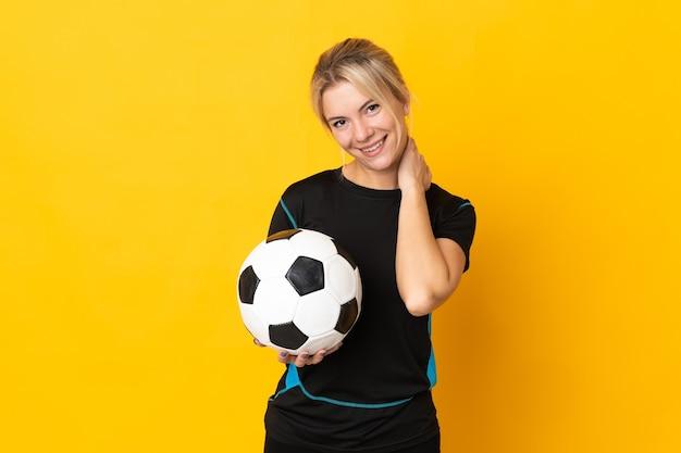 Молодой российский футболист женщина, изолированные на желтом фоне смеясь