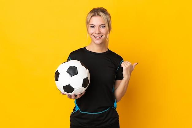 Молодой российский футболист женщина изолирована на желтом фоне, указывая в сторону, чтобы представить продукт