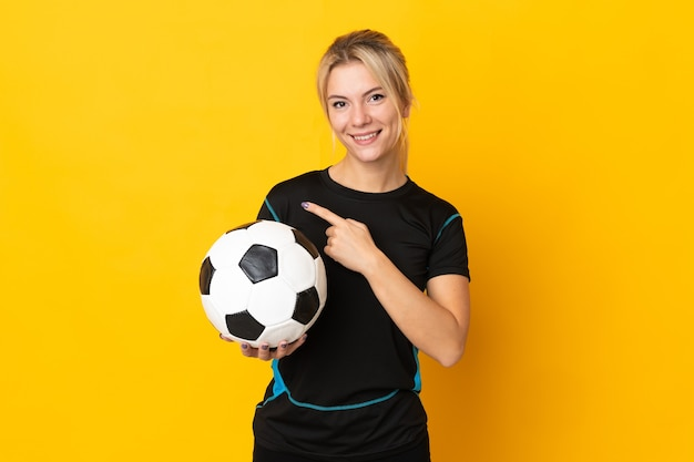 제품을 제시하기 위해 측면을 가리키는 노란색 배경에 고립 된 젊은 러시아 축구 선수 여자