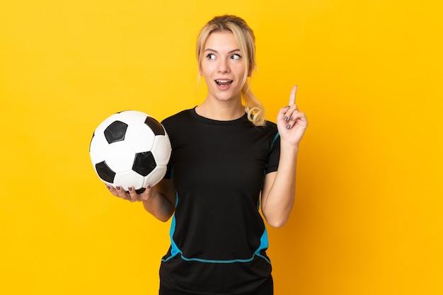 Молодой российский футболист женщина изолирована на желтом фоне, думая об идее, указывая пальцем вверх