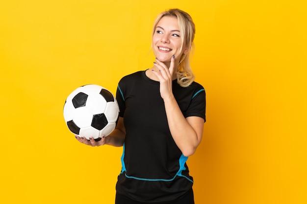 Молодой российский футболист женщина изолирована на желтом фоне, думая об идее, глядя вверх