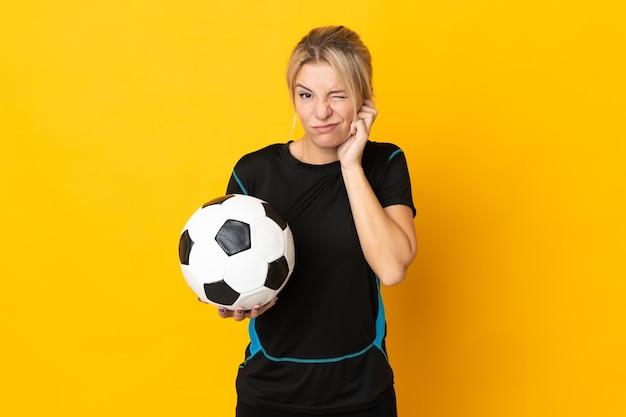 欲求不満と耳を覆う黄色で孤立した若いロシアのサッカー選手の女性