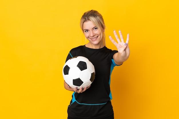 Молодой российский футболист женщина изолирована на желтом счастливом и считает четыре пальцами
