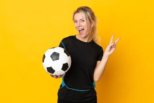 Молодой российский футболист женщина изолирована на желтом, улыбаясь и показывая знак победы