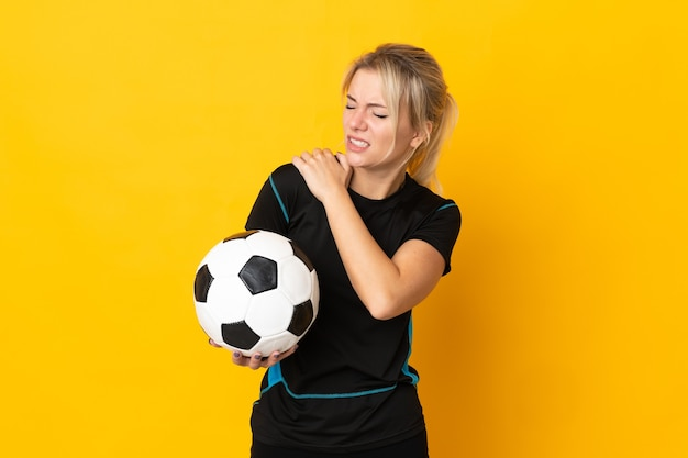 Молодой российский футболист женщина изолирована на желтом, страдает от боли в плече за то, что приложила усилие