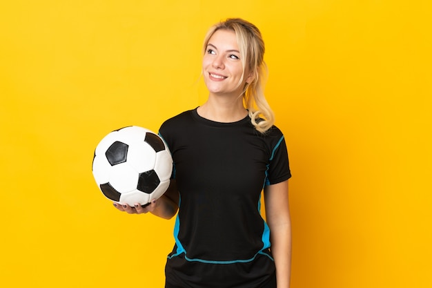 Young russian football player woman isolated on yellow background thinking an idea while looking up