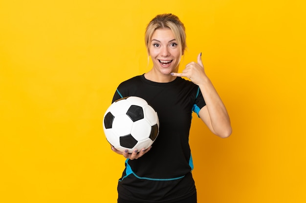Young russian football player woman isolated on yellow wall making phone gesture. call me back sign