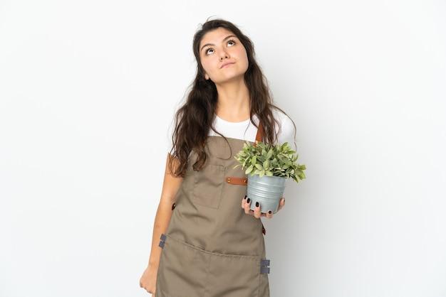 고립 된 식물을 들고 찾고 젊은 러시아 정원사 소녀