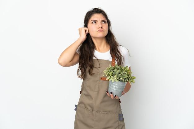 고립 된 식물을 들고 젊은 러시아 정원사 소녀는 좌절과 귀를 덮고