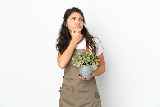의심을 갖는 고립 된 식물을 들고 젊은 러시아 정원사 소녀