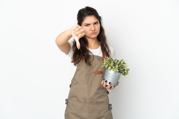 부정적인 표현으로 아래로 엄지를 보여주는 고립 된 식물을 들고 젊은 러시아 정원사 소녀