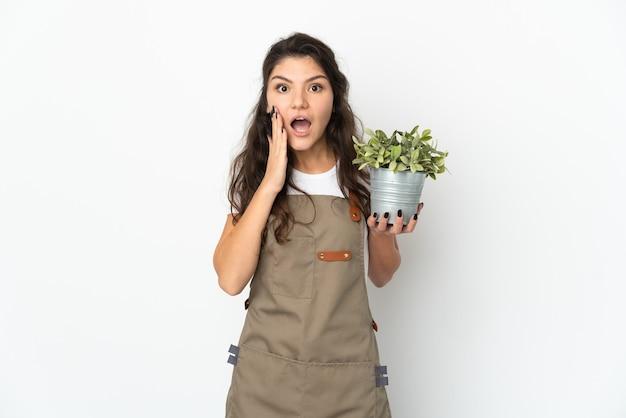 Молодая русская девушка-садовник держит изолированное растение с удивленным и шокированным выражением лица