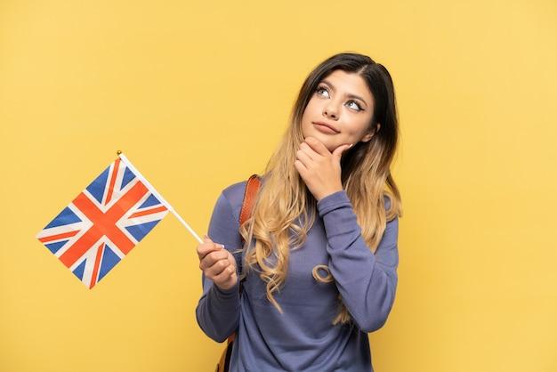 노란색 배경에 고립 된 영국 국기를 들고 찾고 젊은 러시아 소녀