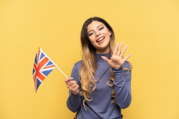 Молодая русская девушка держит флаг соединенного королевства на желтом фоне, считая пять пальцами