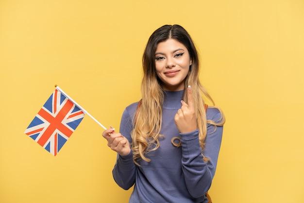 Молодая русская девушка держит флаг соединенного королевства на желтом фоне, делая приближающийся жест