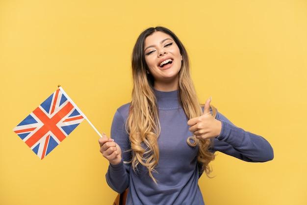 Молодая русская девушка держит флаг соединенного королевства, изолированные на желтом фоне, показывает палец вверх