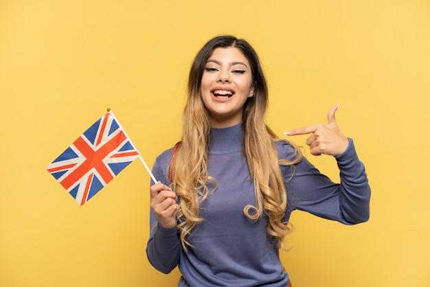 Молодая русская девушка держит флаг соединенного королевства на желтом фоне, показывает палец вверх