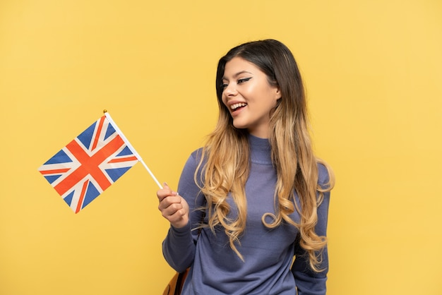 Молодая русская девушка держит флаг соединенного королевства на желтом фоне, смотрит в сторону и улыбается