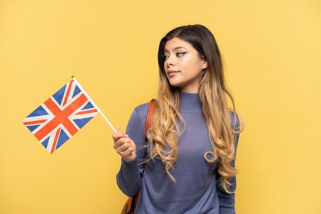 Молодая русская девушка держит флаг соединенного королевства на желтом фоне, глядя в сторону