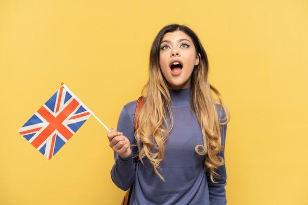 Молодая русская девушка держит флаг соединенного королевства на желтом фоне, глядя вверх и с удивленным выражением лица