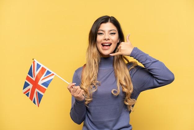 Молодая русская девушка держит флаг соединенного королевства на желтом фоне, делая телефонный жест. перезвони мне знак