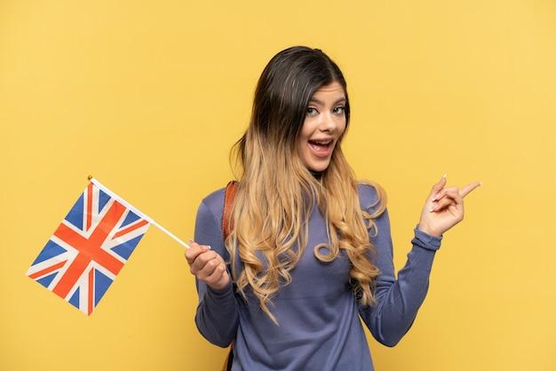 Молодая русская девушка держит флаг соединенного королевства на желтом фоне, указывая пальцем в сторону и представляет продукт