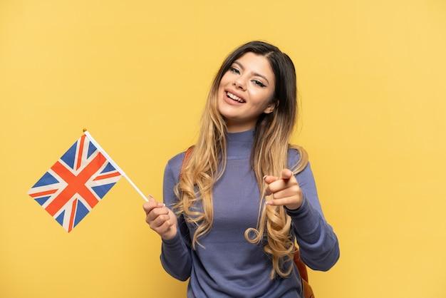 Молодая русская девушка держит флаг соединенного королевства на желтом фоне, указывая вперед с счастливым выражением лица