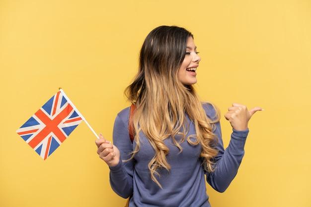 Молодая русская девушка держит флаг соединенного королевства на желтом фоне, указывая в сторону, чтобы представить продукт