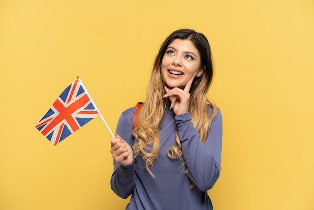 Молодая русская девушка держит флаг соединенного королевства на желтом фоне, думая об идее, глядя вверх