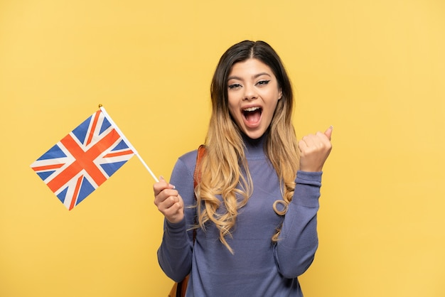 Young russian girl holding an united kingdom flag isolated on yellow background celebrating a victory in winner position
